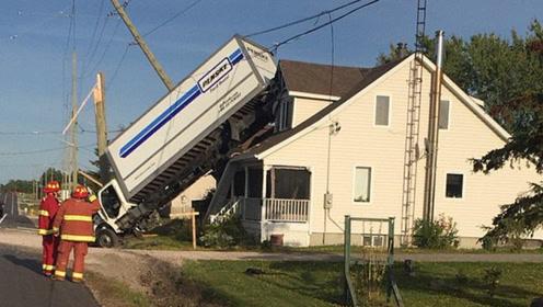 卡车失控撞上电线杆后翻转 落在居民屋顶上