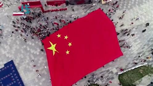 壮观!千人传递巨幅五星红旗 小男孩踮起脚高举国旗致敬