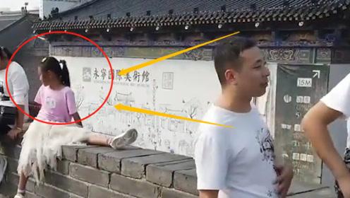 太危险!家长抱孩子站在12米高城墙拍照,保洁:危险但没人听!