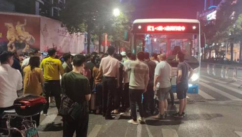 两女子骑车闯红灯被公交车压车底 30多名群众合力抬车救人