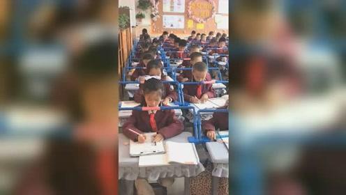 """为防止小学生趴着写字,教室课桌上装""""矫正神器""""走红网络"""