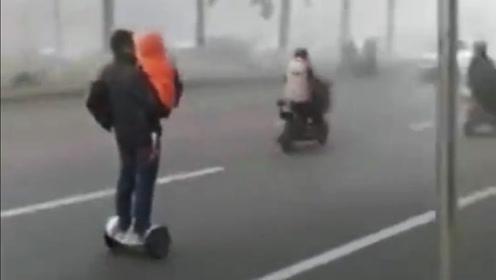 男子抱孩童骑平衡车上路 汽车川流不息场面吓人
