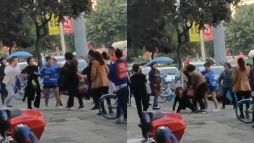 疑因抢客起争执,两司机街边开战,女司机遭疯狂踢打