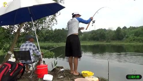 水塘边俩男子撒下钓竿钓鱼,第一竿就收获一条三斤的大草鱼