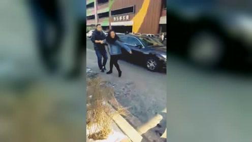 女子为抢车位与人争执 踹车还叫嚣:我有钱打死你!