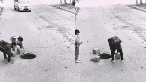 太暖心了!两个小朋友马路上遇无井盖下水道 搬石头将洞口围住