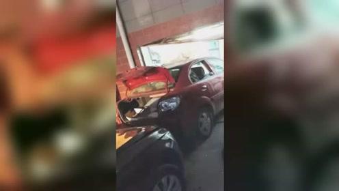惊险!红色小车一头冲进住人车库 只留破损车尾在外