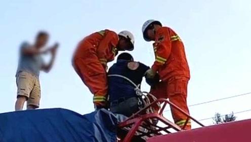 货车司机欲拨开缠车电线时触电,全身麻痹被困车顶