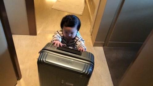 10个月的宝宝推着行李往外走,乍一看还以为要离家出走呢