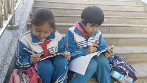 很拼!小学生放学等家长天桥上写作业:回家就只用预习了