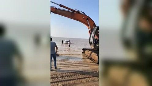 把车开到海边玩,没想到涨潮把车淹了,请挖掘机来拉车!