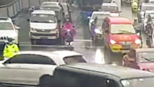暖心一幕!民警冒雨执勤 过路司机给他抛出一把伞