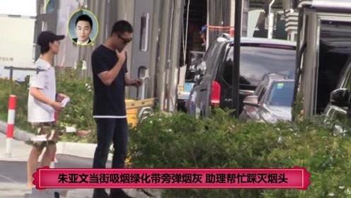 朱亚文当街吸烟绿化带旁弹烟灰 助理帮忙踩灭烟头