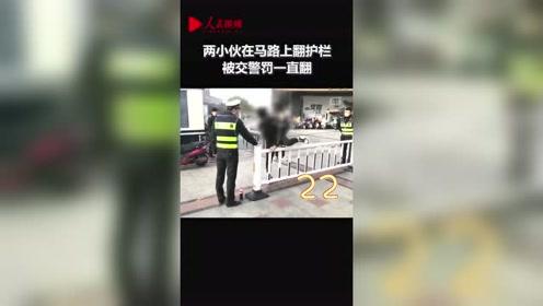 两小伙在马路上翻护栏 被交警罚一直翻 获网友点赞