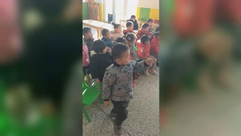 3岁萌娃教室内坐凳子上打拳,不受一旁同学影响不停比划拳脚