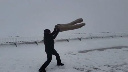 小哥将一条湿透的裤子拿到冰天雪地里,不一会就冻硬了
