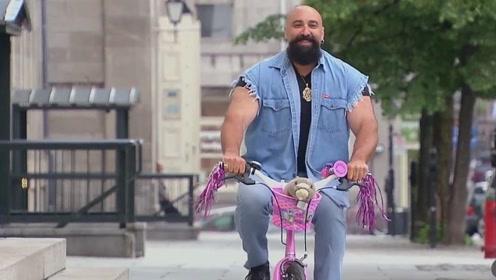 国外街头有位强壮的男子,但是他骑的车子,却是粉色的儿童自行车