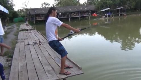 男子与池中鱼王疯狂拉锯战,后面一堆人围观,看着都过瘾