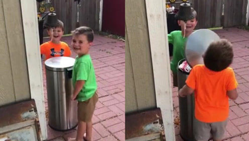 两男孩轮流用垃圾桶盖打对方脸 玩的非常开心