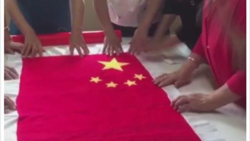 老人亲手缝制国旗表达祝福,历时63天共绣33686针