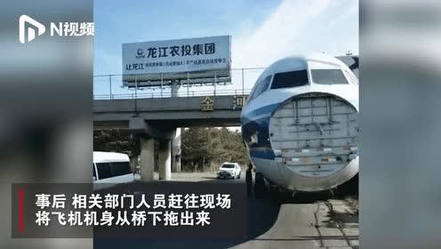 哈尔滨一辆拉运飞机的拖车卡在桥底下,轮胎放气后顺利通过