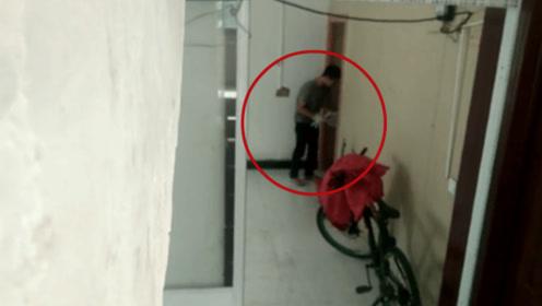 可怕!持刀小偷正在撬门 失主躲在楼梯口拍下视频