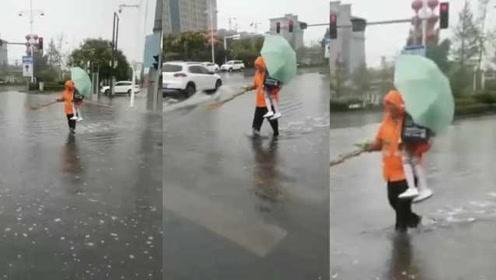暖心!马路积水小女孩路边徘徊,环卫大爷一把抱过马路