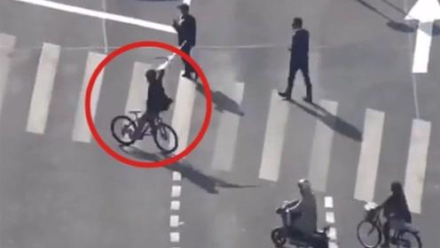 马路上秀杂技?男子倒骑自行车还一边挥舞手中的道具