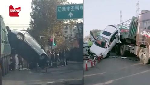 """小轿车遭挤压车身""""倒立""""挂在大货车上,路人吐槽:飞车顶上去了"""