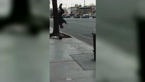 厉害了!一男子倒挂在树上吹笛子