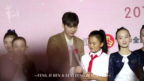 李易峰手握鲜花与春蕾女童一起台上互动,愿春蕾计划越办越好