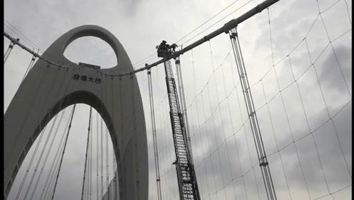 广州一男子爬上猎德大桥50米高吊索  消防员出动云梯成功救援