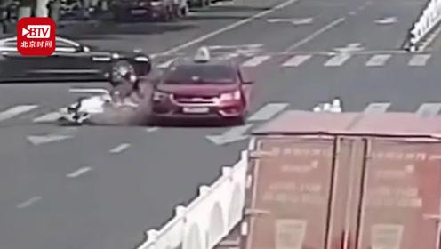 女子骑车逆行被车撞翻又遭另一车卷入车底 众人合力抬车52秒救出