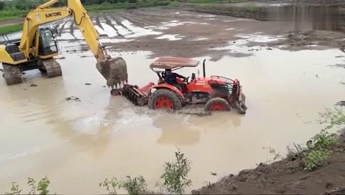 拖拉机陷入泥水中,挖机来帮忙