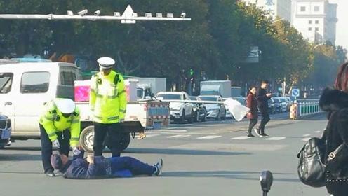 大爷斜穿马路被制止,推搡交警后躺地不起:为什么不要我过马路