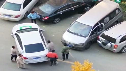 这种乱停车的司机最缺德,车上也不留电话号码,路人只好帮忙抬车了