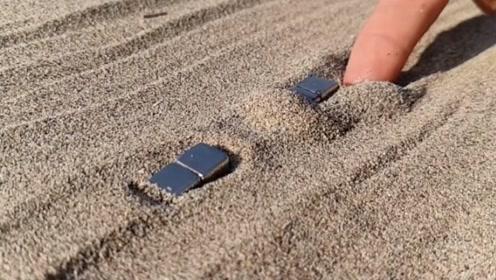 小伙在沙滩上玩磁铁,将磁铁捡起来时,结果意外发生了