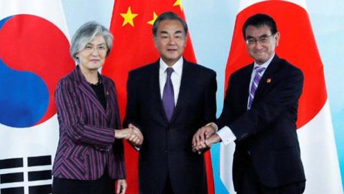 中日韩外长合影 日本外长一时不知该伸哪只手 干脆两手握住王毅