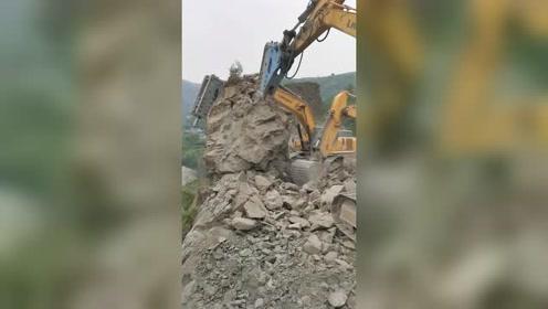 山下是居民房,挖掘机扶住这块大石头不敢动!