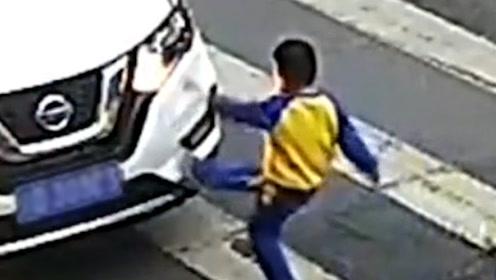 母子走斑马线被轿车撞倒,男孩爬起后怒踹轿车斥责司机