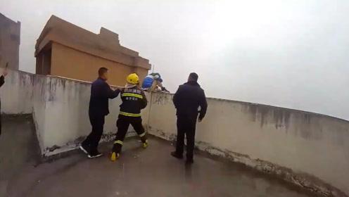 男子坐楼顶边缘欲轻生 消防员一把将其抱住救下