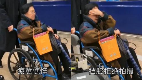 69岁斯琴高娃现身机场,坐轮椅略显疲惫憔悴,用手挡脸拒绝拍摄